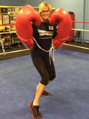 Rock Steady boxing coach and Sweat Therapy owner and founder Kim Bibeau puts on the big gloves.