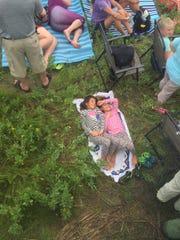 Lucia and Olivia Venevento, 8, of Long Island, New York, wait sleepily for the Pony Swim on Wednesday, July 27, 2016.