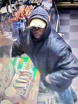 Surveillance image from armed robbery of Orange Mini Mart on Medgar Evers Blvd. in Jackson, Miss.