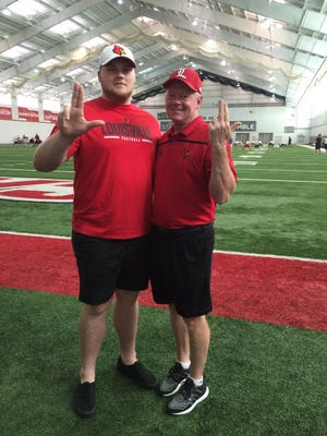 """Belfry 2017 offensive lineman Cole Bentley, left, and Bobby Petrino pose with the Louisville """"L"""" gesture during Bentley's visit to U of L on Sunday, June 12, 2016. He is the Cards' first 2017 in-state pledge."""