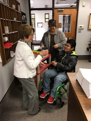 CPHS student Cristian Salamanca delivers a beverage to Suzanne Blaydes, Clinton Prairie Jr./Sr. High's office secretary, with the assistance of Williams.