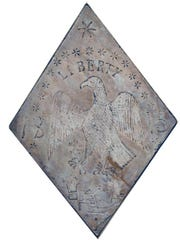 An 1813 sandstone ferry marker with symbols of a new