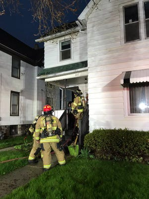 A Fond du Lac Fire/Rescue crew extinguishes a porch fire at 227 Fourth Street Sunday night.