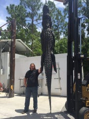 Josh Padrick poses next to a 12-feet, 6-inches-long alligator he caught Monday in Brevard County.