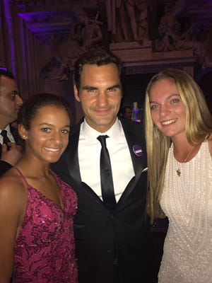 Whitney Osuigwe (left) and Caty McNally (right) pose with Roger Federer at the Wimbledon Champions Ball in mid-July.