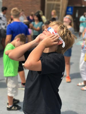 Under spotty cloud cover, a boy watches the eclipse in Salisbury on August 21, 2017.