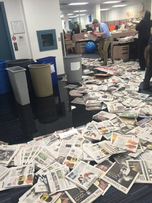 Tennessean reporters and editors place old newspapers out to keep water from spreading Tuesday in the newsroom.