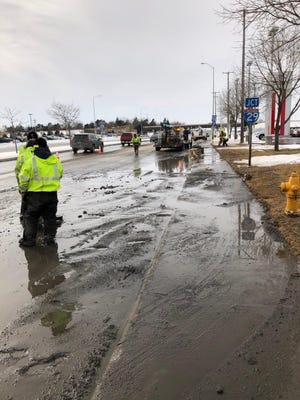 Crews work on repairing a water main break on W. 12th Street.
