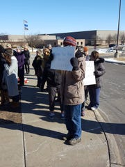 """A parent holds up a sign that says """"Thank you for being leaders"""" to the students that participated in a school walkout to raise awareness about gun violence on Wednesday at Marshfield High School."""