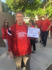 Teacher Alex Kimble from Willis Junior High holds up a sign calling attention to low teacher salaries while marching in solidarity with #RedForEd March 26, 2018, in Chandler.