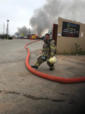 Parker District Fire Department firefighter Rick Hopkins works a large fire at a scrap metal recycling business that sent plumes of smoke into the sky near White Horse Road.