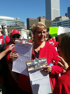 Poudre School District Board of Education member Cathy Kipp hands out petitions during a downtown Denver rally earlier this year to get Amendment 73, which includes a graduated tax increase to fund education, on the November ballot.