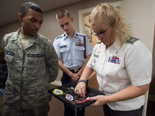 Pensacola Civil Air Patrol Cadet Squadron cadets Jaiden Muniz-Walls, left, and Micah Barr look on as Capt. Mia Ottesen, right, prepares a tray of awards, devices and badges for a group of cadets to be honored during the organization's meeting Tuesday, Nov. 7, 2017.