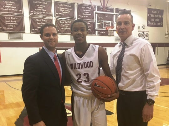 The latest Wildwood boys' basketball player to reach the 1,000-point mark, Kyion Flanders celebrates the accomplishment with athletic director Travis LaFerriere, left, and coach Scott McCracken.