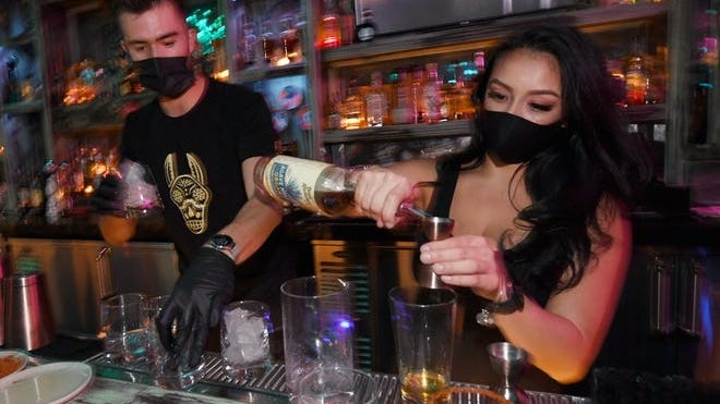 Barback Jaime Torres (L) and bartender Brandi Sterner make drinks after the bartop opened for the first time at Lucky Day bar in the Fremont East Entertainment District on Sept. 21, 2020 in Las Vegas, Nev. Last week, Nevada's COVID-19 Mitigation and Management Task Force voted to allow bars and lounges in Clark County to reopen at 11:59 p.m. on Sunday because of declining coronavirus numbers. The vote removes the last of the bar closure orders re-imposed by Nevada Gov. Steve Sisolak in July due to increasing COVID-19 cases.