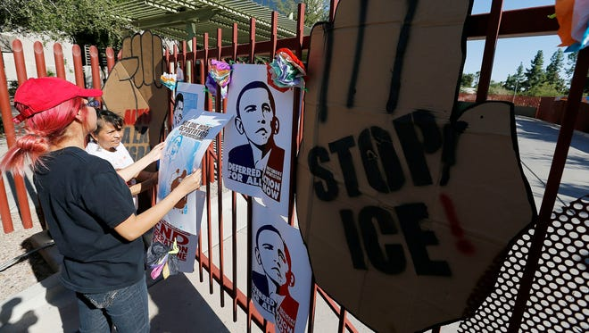 Protesters hang signs at the main gate of the U.S. Immigrations and Customs Enforcement office in Phoenix on Oct. 14 with a goal of stopping future deportations.