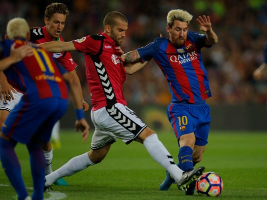 FC Barcelona's Lionel Messi, right, duels for the ball against Alaves's Victor Laguardia during the Spanish La Liga soccer match between FC Barcelona and Alaves at the Camp Nou in Barcelona, Spain, Saturday, Sept. 10, 2016. (AP Photo/Manu Fernandez)