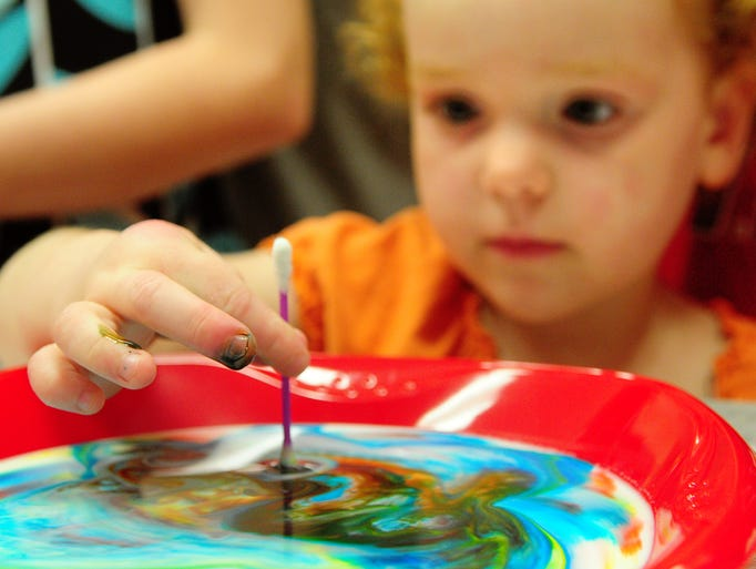 """Abigail Albright, 3, participates in a """"Magic Colored Milk"""" science experiment at the Hattiesburg Library Saturday afternoon during Mad Scientist Day."""