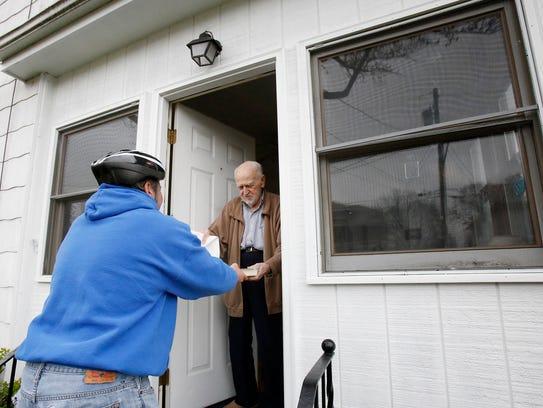 Elmira Mayor Dan Mandell hands Lincoln Street resident