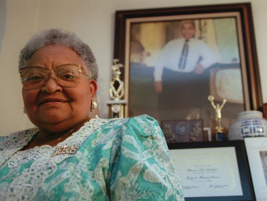 Mamie Till Mobley stands before a portrait of her slain