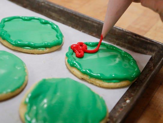 Mary Freitag decorates wreath Christmas cookies Thursday,