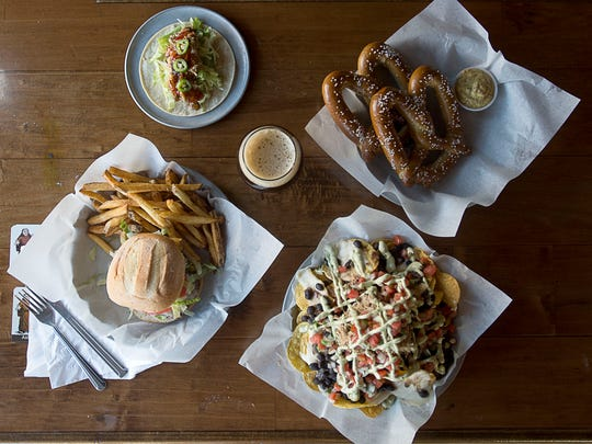 Pub food classics at the Thirsty Monk's Biltmore Park location include a hamburger with fries, a Thai pulled pork taco, Fat Tire nachos with pulled pork, and pretzels with mustard.
