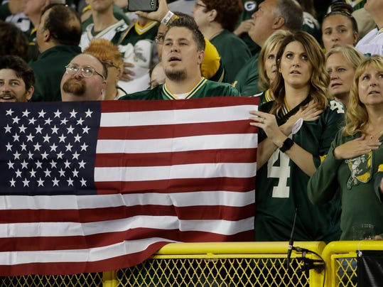 Fans hold a flag during the national anthem before an NFL football game between the Green Bay Packers and the Chicago Bears Thursday, Sept. 28, 2017, in Green Bay, Wis. (AP Photo/Morry Gash)