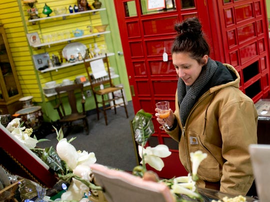 Elizabeth McDonald, of Marine City, sips on a mimosa while looking over antiques with family during the Gourmet Gallop Thursday, Dec. 3, 2015, at Angels Among Us in St. Clair.