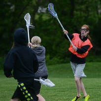 Montana Meyer (right) throws the ball past Marin Ehrmantraut during a recent lacrosse practice at Riverdale Park.