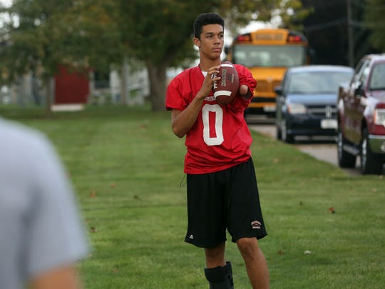 Washington High School freshman quarterback Trashaun Willis plays catch while wearing a protective boot at football practice in October. Willis, who made headlines in February after a video of him dunking a basketball went viral, broke his ankle earlier in the football season.