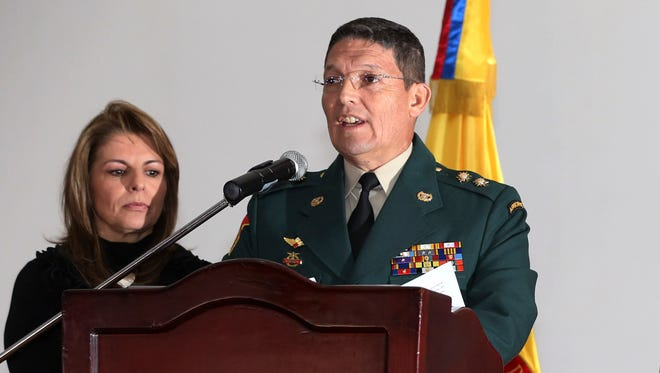 Army Gen. Ruben Alzate reads a statement at the military hospital in Bogota accompanied by his family on Monday.