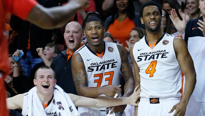 Oklahoma State guard Phil Forte (13), guard Marcus Smart (33) and wing Brian Williams (4) cheer on the bench following a dunk by teammate Le'Bryan Nash in the second half of an NCAA college basketball game against Texas Tech in Stillwater, Okla.