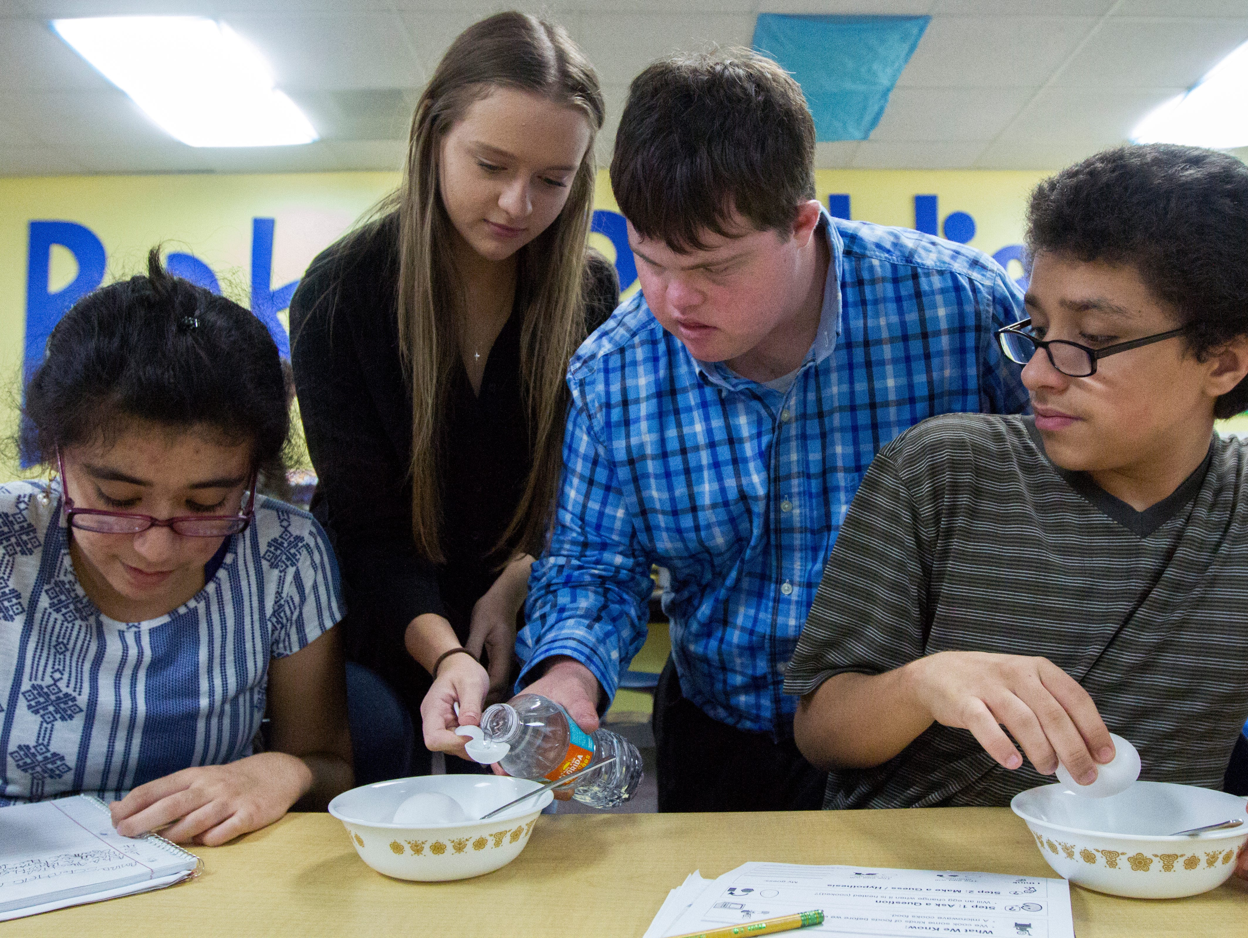 Christian Diggs helps pour water alongside Kendal Hammond during a class experiment as part of Mrs. Molly Haskill's English class at Ida Baker High Schoo lin Cape Coral on Tuesday, Oct. 11. Classmates Amina Mohamed,left, and Lazaro Hernandez were also participating.