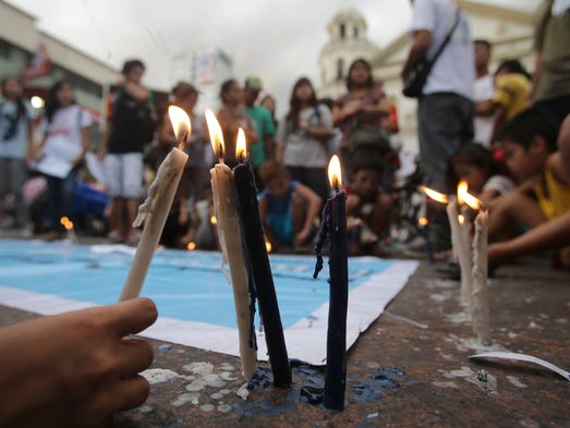 A Filipino boy joins activists lighting candles in downtown Manila. Protesters are calling for the continued aid and rehabilitation of typhoon-ravaged Tacloban and nearby provinces in central Philippines.