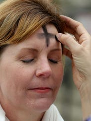 Roxane Fidler receives a sign of the cross in ashes