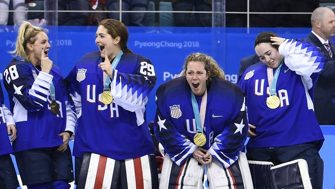 Members of team USA celebrate on the podium during the medal ceremony after the US team won the women's ice hockey event during the Pyeongchang 2018 Winter Olympic Games at the Gangneung Hockey Centre in Gangneung on February 22, 2018.   / AFP PHOTO / Brendan SmialowskiBRENDAN SMIALOWSKI/AFP/Getty Images ORIG FILE ID: AFP_10T7AC