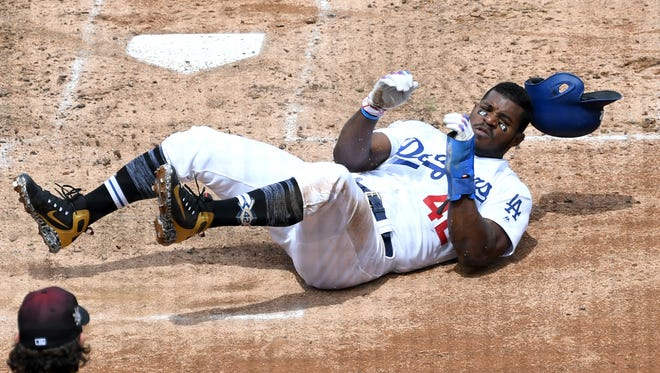 Apr 15, 2018: Los Angeles Dodgers right fielder Yasiel Puig is safe at home after tagging up from third on a sacrifice fly by Los Angeles Dodgers second baseman Chase Utley in the second inning of the game against the Arizona Diamondbacks at Dodger Stadium.