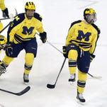 Michigan's Phil Di Giuseppe, right, celebrates with teammates Brennan Serville (6) and Nolan De Jong (21) after scoring the winning goal  during the third period of a college hockey game Thursday, Jan. 23, 2014, in Detroit. Michigan defeated Michigan State, 2-1.