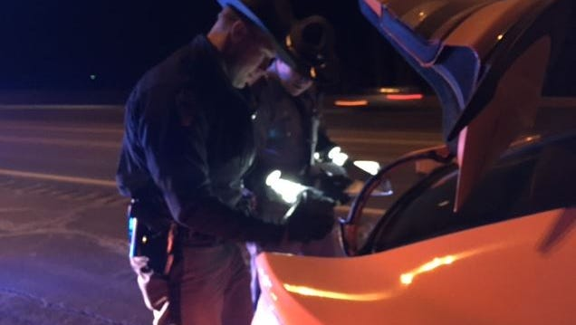 Sgt. Daniel Kumor of the Ashland post of the Ohio  Highway Patrol and a fellow trooper search the trunk of a car that was stopped by spike strips on I-71 Friday near Ohio 97 exit following a high school pursuit.