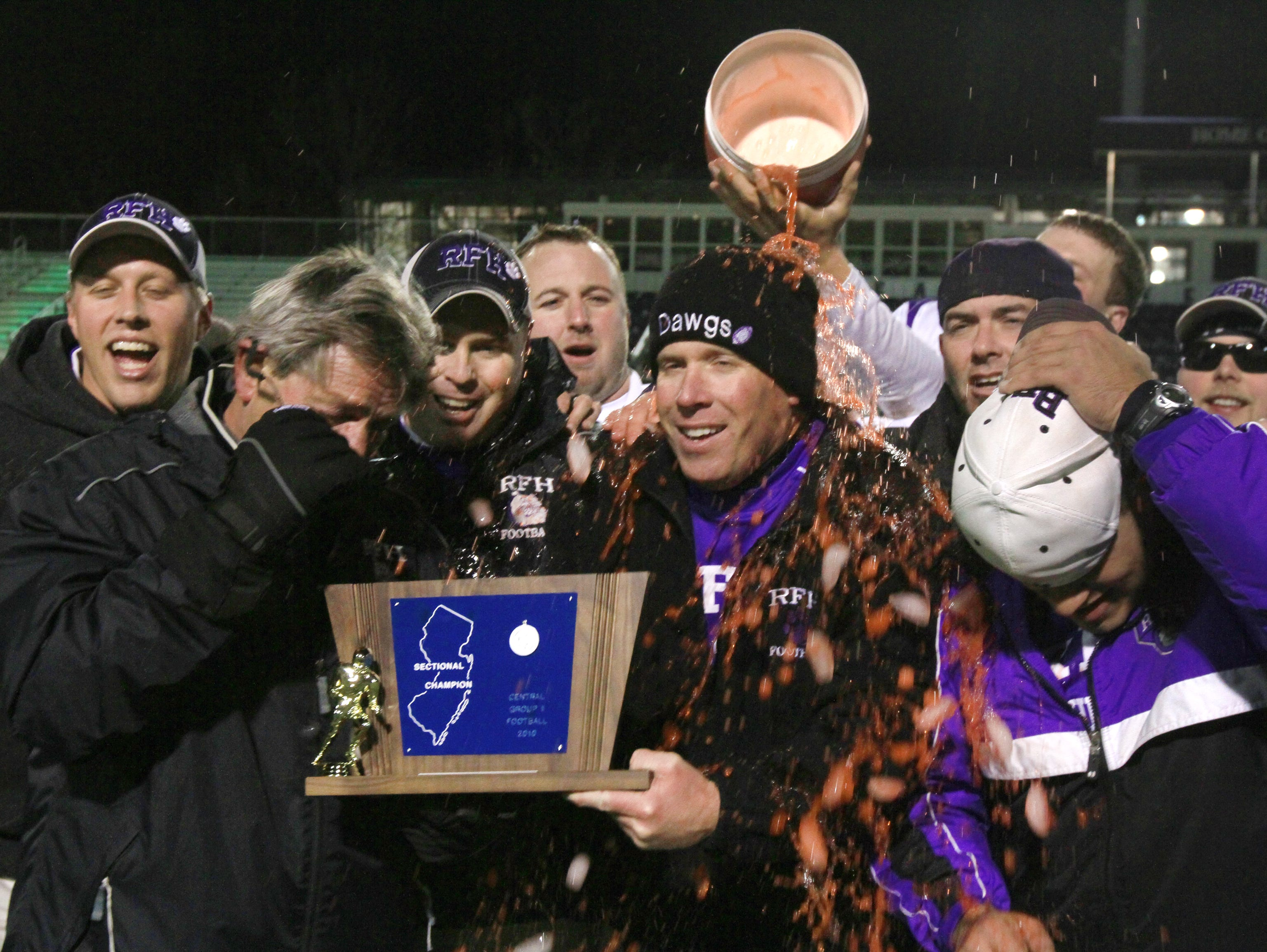 Rumson-Fair Haven coach Shane Fallon (center) gets a Gatorade bath as he receives the trophy after their upset win over Matawan in the 2010 CJ Group II championship game.