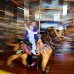 Zoe Nickler, 2, waves as she enjoys a carousel ride with her mother Heidi on Thursday at the Richland Carrousel Park.