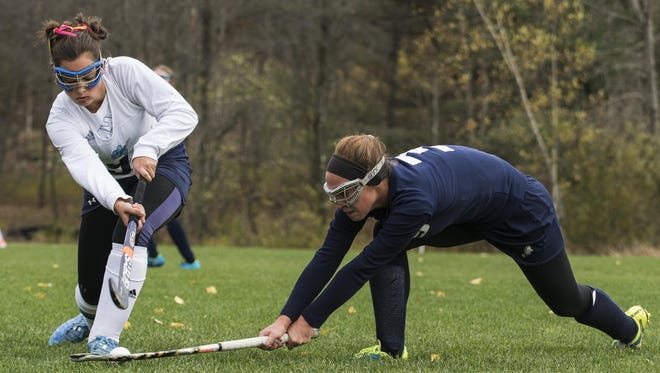 Burlington's Hannah Schriling, right, battles for the ball with MMU's Margaret Thompson (9) during a Division I high school field hockey playoff game in October.