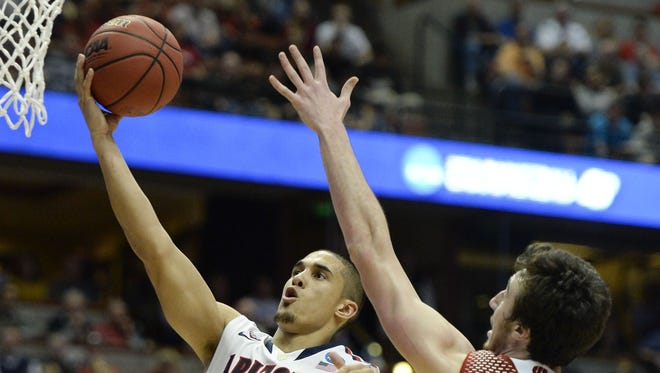 Arizona Wildcats guard Nick Johnson (13) shoots the ball against Wisconsin Badgers forward Frank Kaminsky (44) during the second half in the finals of the west regional of the 2014 NCAA Mens Basketball Championship tournament at Honda Center on March 29, 2014.