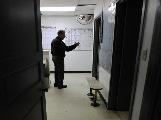 Fairfield County Sheriff's Office Chief Deputy Jerry Perigo talks about the how the holding cells in the booking area of old Main Street Jail were used Tuesday, Oct. 31, 2017, in Lancaster. The old jail was opened to the public for tours Tuesday night.