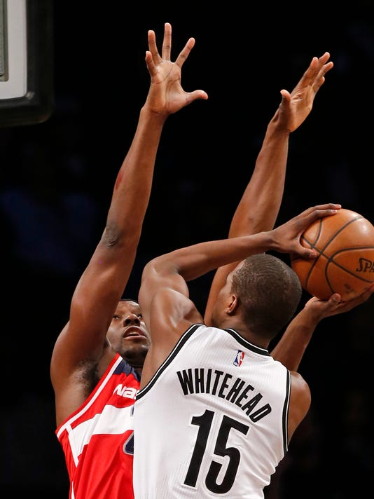 CORRECTS WIZARDS PLAYER TO IAN MAHINMI, INSTEAD OF OTTO PORTER JR. - Washington Wizards forward Ian Mahinmi, left, defends Brooklyn Nets guard Isaiah Whitehead (15) during the first half of an NBA basketball game, Wednesday, Feb. 8, 2017, in New York. (AP Photo/Kathy Willens)
