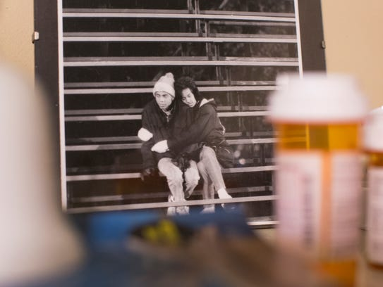 A photo of Christopher and Pamela early in their marriage sits on their mantel. In the foreground are medications.