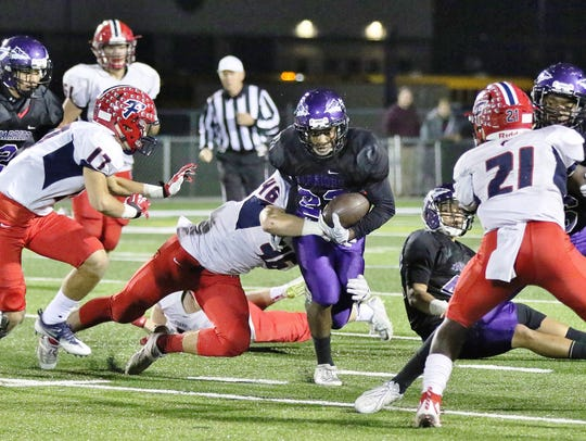 Woodhaven's Raekwon Castelow (middle) is tackled by
