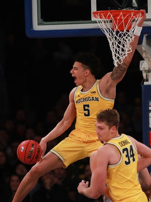 Michigan's  D.J. Wilson reacts after a dunk against the Marquette Golden Eagles in the second half during the 2K Classic at Madison Square Garden in New York.