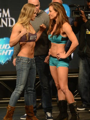 Ronda Rousey and Miesha Tate face off after the weigh-in for their UFC women's bantamweight title fight at MGM Grand Garden Arena.