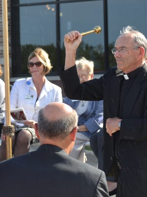 The Most Rev. Robert F. Morneau sprinkles holy water as part of the blessing at the 2014 dedication of St. Clare Memorial Hospital in Oconto Falls